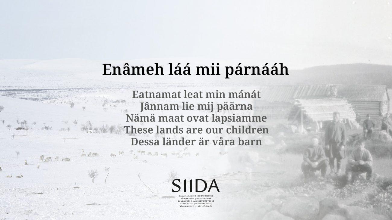 Teksti: Enâmeh láá mii párnááh – Nämä maat ovat lapsiamme, kolmella saamenkielellä, sekä suomeksi ja englanniksi. Tekstin taustalla vanha mustavalkokuva saamelaisalueelta.
