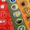 Diagonaalisti päällekkäin tasossa, kirkkaanpunainen, oliivinvihreä ja oranssi tuubihuivi, joihin on painettu Suomen kansallispuistojen ja luonnonpuistojen logot