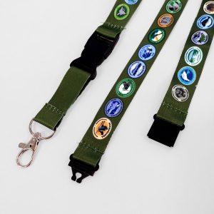 Oliivinvihreä avainnauha, jossa on suomen luonnonpuistojen ja kansallispuistojen logot