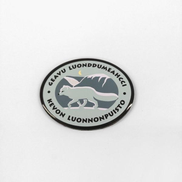 Pieni metallinen ovaalin muotoinen magneetti, ossa on Kevon luonnonpuiston logo. Logossa on naalin kuva