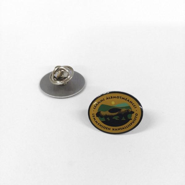 Pieni metallinen pinssi, jossa on Lemmenjoen kansallispuiston logo. Logossa on ahman kuva