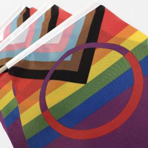 Kirkasvärinen Pride versio saamenlipusta. Kolme sateenkaarenväristä lipua lähikuvassa