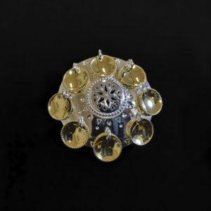 Pieni hopeinen rintakoru, risku, jossa on keskellä lumihiutaletta muistuttavaa ornamentiikkaa. Riskussa on 8 kullattua laukkasta
