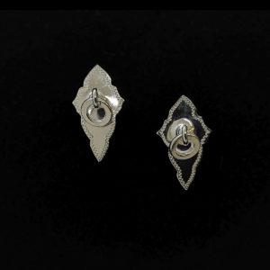 Hopeiset salmiakin muotoiset nappikorvakorut, joissa on kaiverrettu reunus ja keskellä hopeinen lenkki. Korut ovat saaneet muotonsa usein miesten saamenpuvussas olevista soljista ja niissä roikkuvista koristeista