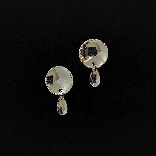 Pyöreät hopeiset nappikorvakorut, joissa on koristereunus ja pisaran muotoinen roikkuva laukkanen alareunassa